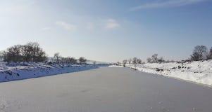 Een bevroren rivier in gevangenschap dichtbij de koude Sneeuw en blauwe hemel met wolken en stok Ik houd van op een bevroren rivi stock afbeeldingen