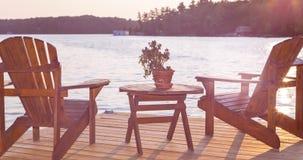 Een bewegend beeld van Muskoka-stoelen op een dek die Meer Rosseau, Ontario overzien, bij zonsondergang met sunflare stock video