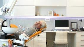 Een bewegend schot op een schuif die een jonge mensenzitting als tandartsenvoorzitter tonen, onderzoekt hij camera en glimlacht stock videobeelden