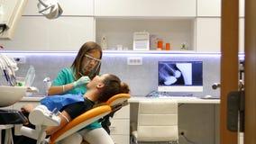 Een bewegend schot in een tandartsenbureau, een jonge vrouwelijke tandarts die en aan de patiëntentanden onderzoeken werken stock footage