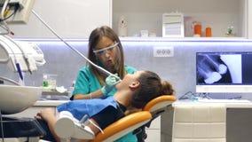Een bewegend schot in een tandartsenbureau, een jonge vrouwelijke tandarts die en aan de patiëntentanden onderzoeken werken, het  stock video