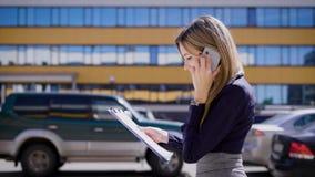 Een bezige bedrijfsdamebesprekingen op haar mobiele telefoon, die belangrijke contracten houden, loopt zij door het parkeerterrei stock video