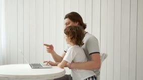 Een bezige Jonge mens werkt thuis aan laptop en behandelt ook zijn zoon stock footage