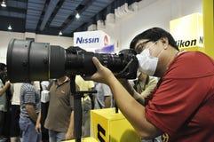 Een bezoeker die de camera en de lens van Nikon test Royalty-vrije Stock Fotografie