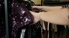 Een bezoeker van een kledingsopslag kiest de goederen op de hanger stock videobeelden