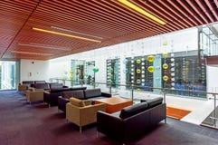 Een binnenland van een bureaugebouw met leunstoelen, houten banken, stock fotografie