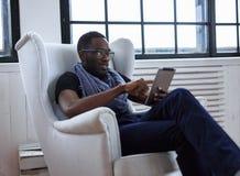 Een blackman zitting op de stoel stock afbeeldingen