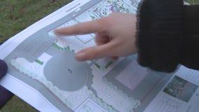Een blad van document met een algemeen plan voor het groen maken van het park Bespreek het plan voor het planten van bomen in het stock video