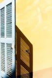 Een blauw blind die een schaduw op een okermuur gieten Royalty-vrije Stock Fotografie