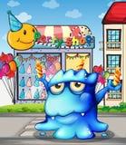 Een blauw monster die de kaarsen voor de partijwinkel in evenwicht brengen Stock Fotografie