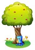Een blauw monster die onder de boom snikken Stock Foto
