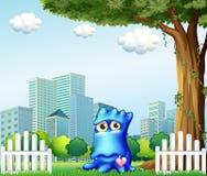Een blauw monster die zich dichtbij de omheining over de lange gebouwen bevinden Stock Fotografie