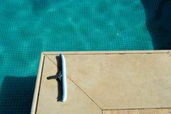 Een blauwe borstel met een spons voor het schoonmaken van het schoonmaken van de pool die de tegels op de achtergrond van de pool royalty-vrije stock afbeelding