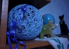 Een blauwe decoratieve bal van draden en een beeldje van een olifant op een plank royalty-vrije stock foto's