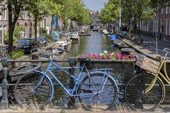 Een blauwe fiets naast een kanaal in Amsterdam royalty-vrije stock afbeeldingen