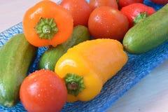 Een blauwe glasplaat met heldere veelkleurige groenten stock foto
