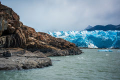 Een blauwe gletsjer dichtbij een rotsachtige kust Shevelev stock fotografie