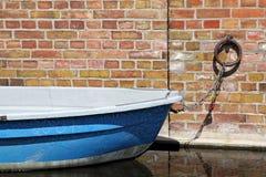 Een blauwe het roeien boot wordt gedokt bij een bakstenen muur Royalty-vrije Stock Afbeeldingen