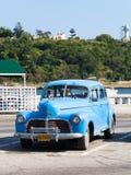 Een blauwe klassieke auto op malecon in de stad Cuba van Havana Stock Afbeeldingen