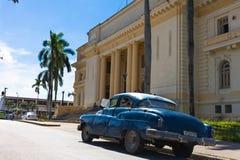 Een blauwe klassieke die auto oldtimer voor het overheidshuis wordt geparkeerd Stock Foto