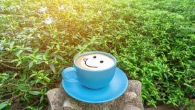 Een blauwe kop van koffie met bruin het glimlachen gezicht op wit melkschuim, op groene bladerenstruik onder zonlichtochtend stock afbeeldingen