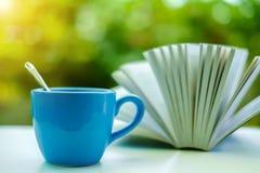 Een blauwe kop van koffie met vaag geopend boek stock foto's