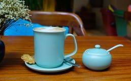 Een blauwe kop van koffie op houten lijst bij koffiewinkel Stock Foto's