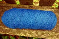 Een blauwe streng van garens op een grijze raad van een bank stock fotografie