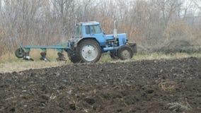 Een blauwe tractor ploegt zwarte grond in de diepe herfst De voorbereiding van de de wintergrond stock video