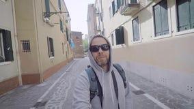 Een blije boertoerist loopt door een Europese stad Een mens neemt zich op een selfiecamera en glimlacht Smartphones stock footage