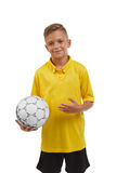 Een blije die jongen met een voetbalbal over de witte achtergrond wordt geïsoleerd Een tiener in een sportkleding Actief levensst royalty-vrije stock afbeeldingen