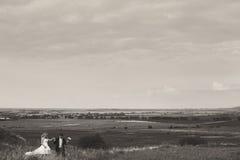 Een blik van ver op het huwelijkspaar die op het gebied lopen Stock Fotografie