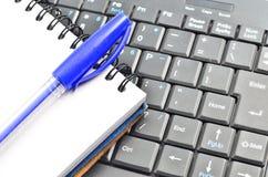 Een blocnote en een toetsenbord van een computer stock fotografie