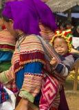 Een bloem hmong en haar baby bij Bac Ha Week-eindmarkt Stock Foto's