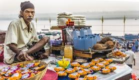 Een bloemverkoper zit op een platform boven de Rivier van Ganges met gekruiste benen het verkopen van zijn bloemen en kaarsen in  stock afbeelding