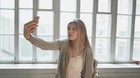 Een blond blonde op het tegenovergestelde venster maakt selfie gebruikend een smartphone De mooie jonge vrouw schiet zich bij stock video