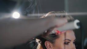 Een blond meisje draait haar haar rond kapper Een stilist maakt tot een kapsel aan een vrouw die haar haar krullen die omhoog kru stock footage
