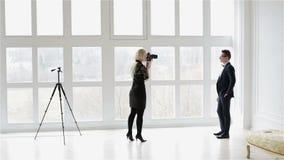Een blond meisje in een zwarte kleding neemt foto's van een mens in een kostuum dichtbij een groot venster stock videobeelden