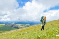 Een blond meisje in een groen jasje neemt alleen toe de berghelling in t Stock Afbeelding