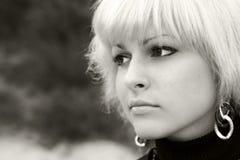 Een blond meisje kijkt in afstand Stock Foto