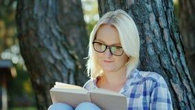 Een blonde jonge vrouw in glazen leest een boek in het park Zit dichtbij een boom, mooi licht vóór zonsondergang stock videobeelden