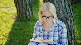 Een blonde jonge vrouw in glazen leest een boek in het park Zit dichtbij een boom, mooi licht vóór zonsondergang Hoogste mening stock video