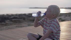 Een blonde jongen drinkt water van een fles stock video