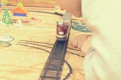 Een blonde jongensspelen met een stuk speelgoed trein in een ruimte op het tapijt stock afbeeldingen