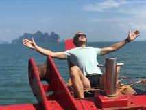 Een blonde kerel in zonnebril en een t-shirt openden zijn handen voor de zon aan boord van het schip op een hete dag tegen de ach stock foto
