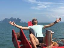 Een blonde kerel in zonnebril en een t-shirt openden zijn handen voor de zon aan boord van het schip op een hete dag tegen de ach stock afbeelding