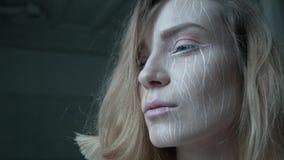 Een blonde met artistieke samenstelling heft haar hoofd op en kijkt dapper vooruit Een jonge vrouw is volledig van bepaling in ha stock footage