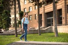 Een blonde schooljongen, dragend in een overhemd en jeans, gangen met een kn stock foto's