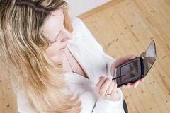 Een blonde vrouw die een pda gebruikt. Stock Afbeeldingen