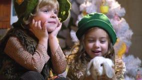 Een blondejongen in een ouderwetse feestelijke kledij zit naast een meisje die een witte kriik in haar wapens houden, langzame mo stock videobeelden